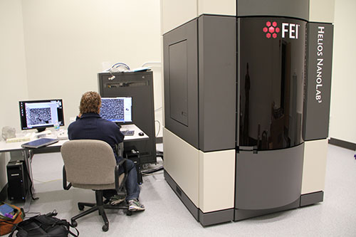 A technician from FEI runs tests on the new focused ion beam microscope. The images on screen were produced by the new equipment.